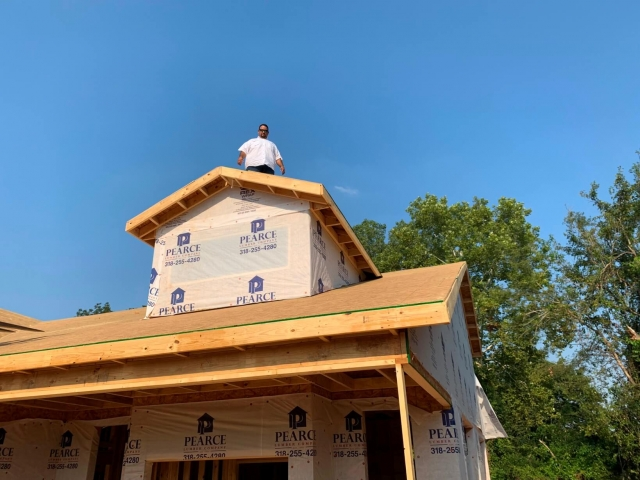 Worker standing on roof of house