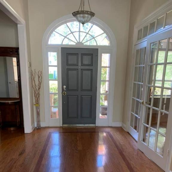 A front door with decorative surrounding windows
